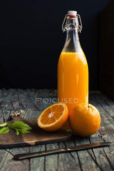 Garrafa de suco de laranja cítrico fresco colocada perto de metades de laranjas frescas em uma mesa rústica escura de madeira no fundo escuro — Fotografia de Stock