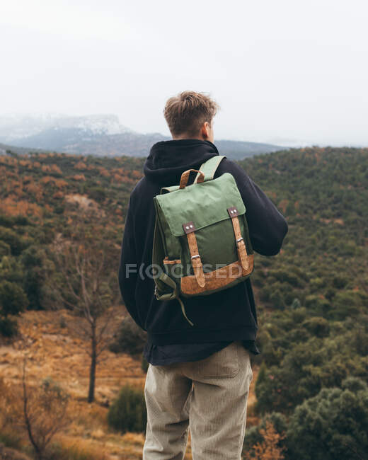Back view of young male hiker with backpack standing on hill and enjoying beautiful autumn landscape while travelling in mountains — Stock Photo