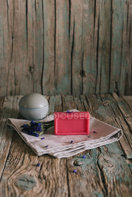 Plate with aromatic organic soap and flowers placed on napkin on shabby lumber table near cup with ingredient — Stock Photo