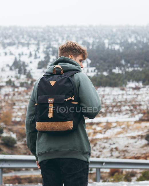 Vista trasera de un joven excursionista en ropa interior cálida con mochila de pie junto a la carretera de carretera con campo nevado y bosque en el fondo en el día nublado - foto de stock