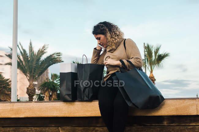 Mujer joven de pelo rizado satisfecho en ropa casual sonriendo mientras se utiliza el teléfono móvil en el banco con bolsas de compras en el muelle moderno - foto de stock