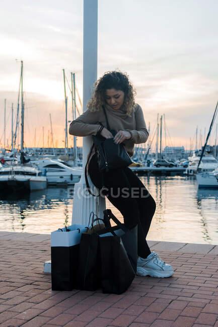 Vista lateral de la mujer joven con estilo en traje casual apoyado en el poste mientras revisa la mochila en el muelle moderno después de ir de compras - foto de stock
