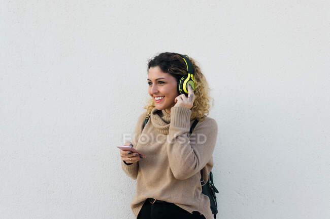 Jovem mulher feliz em camisola casual bege sorrindo ao usar fones de ouvido e telefone celular com parede branca no fundo — Fotografia de Stock