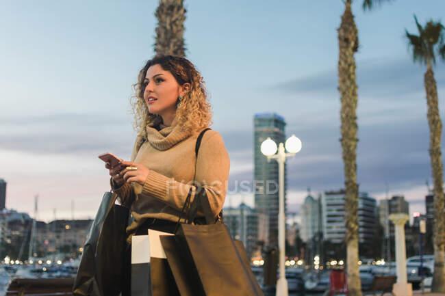 Vista lateral de la joven feliz mirando hacia otro lado con bolsas de compras riendo mientras que los mensajes de texto en el teléfono móvil con la ciudad moderna en el crepúsculo en el fondo - foto de stock