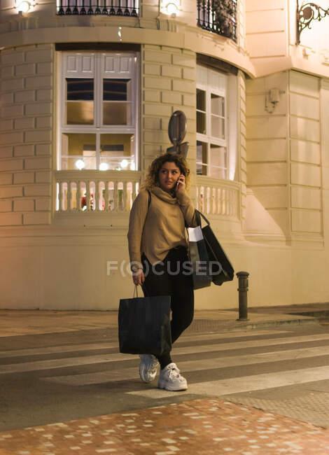 Радісна молода жінка, одягнена в повсякденне вбрання, сміється, розмовляючи по мобільному телефону з сумками в руках на вулицях міста. — стокове фото