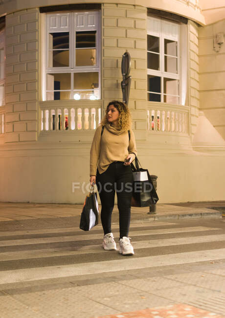 Joyful young woman in casual wear looking away while crossing a zebra crossing with mobile phone on hands and shopping bags at city street — Stock Photo