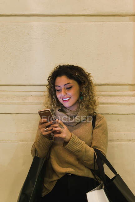 Satisfied curly haired young woman in casual wear smiling while using mobile phone with shopping bags leaning on wall — Stock Photo