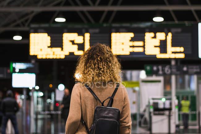 Rückansicht einer anonymen Reisenden mit Rucksack an Bord mit Fahrplan im Flughafenterminal — Stockfoto
