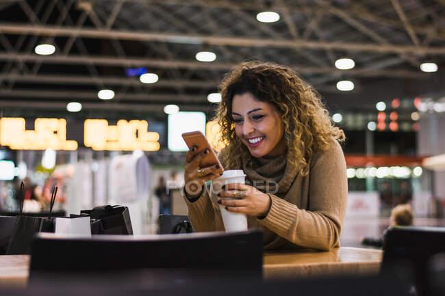 Señora contemporánea en suéter beige casual usando el teléfono móvil en la mesa con café para ir en el aeropuerto sobre fondo borroso - foto de stock