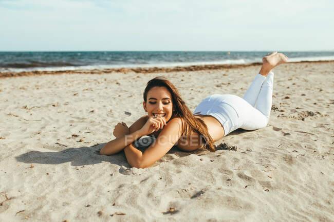 Счастливая молодая чувствительная женщина в белых джинсах, лежащая на песчаном пляже под солнечным светом — стоковое фото