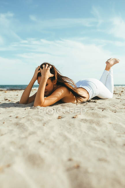 Счастливая молодая чувствительная топлесс женщина в белых джинсах лежит на песчаном пляже под солнечным светом — стоковое фото
