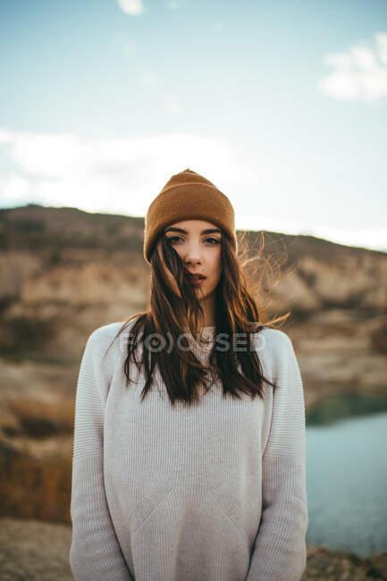 Jeune touriste charmante femme regardant la caméra tout en appréciant voyage week-end au lac en automne — Photo de stock