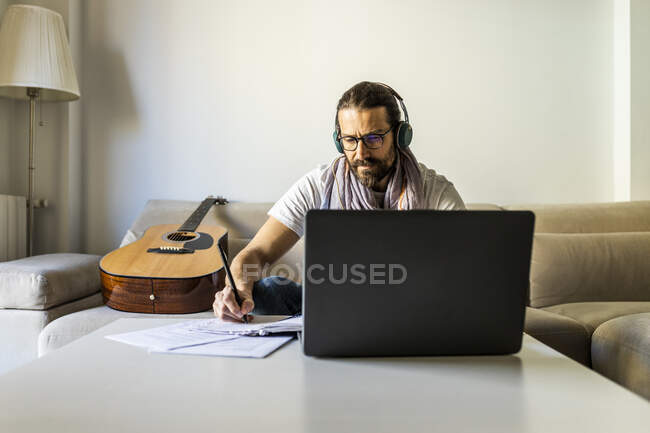 Contemporary man with guitar writing chords in living room — Stock Photo