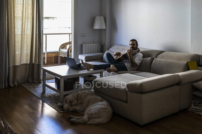Stylish guitarist on couch in living room — Stock Photo