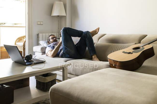 Homme écrivant des notes sur le canapé dans le salon confortable — Photo de stock
