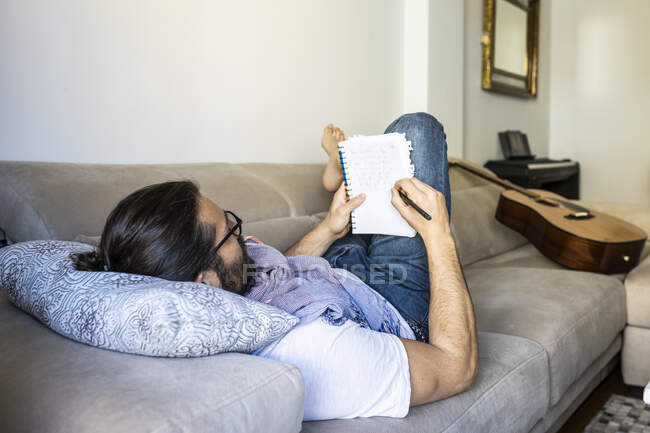 Back view of smart bearded man in casual wear lying on comfortable couch while taking notes in stylish living room — Stock Photo