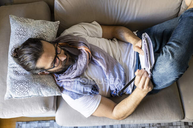 Man writing notes on couch in cozy living room — Stock Photo