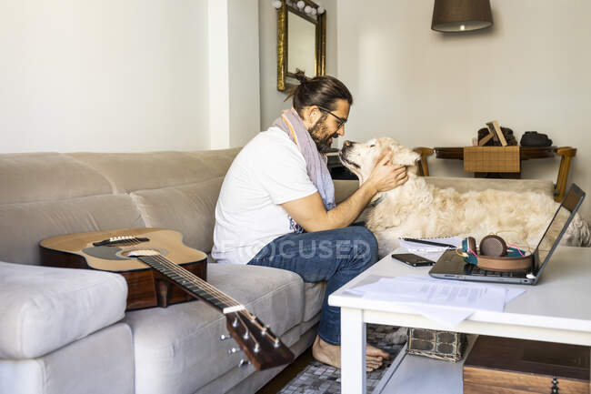 Side view of happy bearded man in casual wear sitting on couch and smiling while cuddling with big Golden Retriever in modern living room — Stock Photo