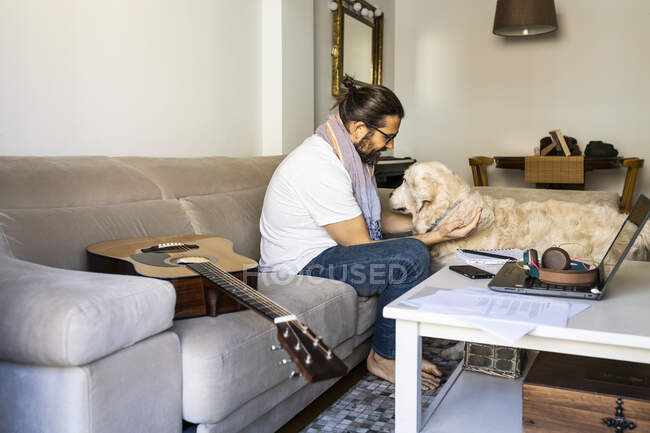 Satisfied guy petting Retriever at home — Stock Photo