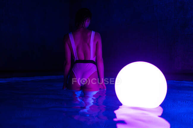 Back view of slim woman in swimsuit standing in dark thermal bath pool with luminous ball on water — Stock Photo