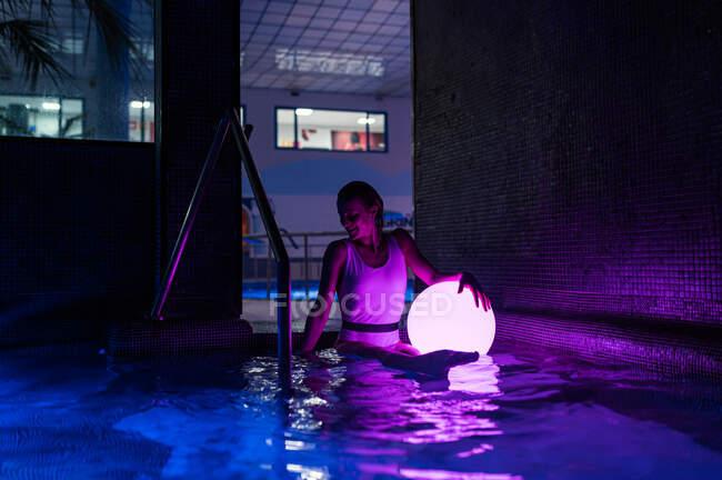 Спокійна молода жінка в купальнику тримає блискучу кулю, стоячи в темному басейні з неоновим світлом. — стокове фото