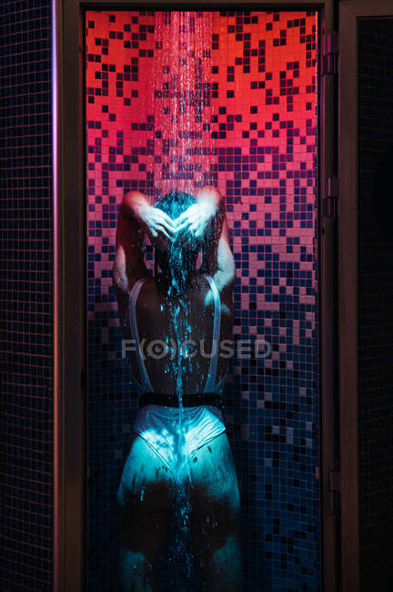 Back view of young woman in swimwear enjoying water and relaxing in shower cabin illuminated with red and blue light — Stock Photo