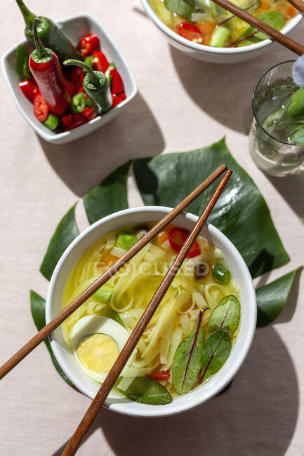 From above top view oriental ramen healthy noodles soup with shiitake, spinach, carrots, eggs and chillies on restaurant table — Stock Photo