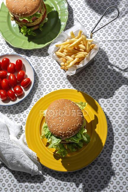 З верхнього виду домашній веганський зелений сочевичний бургер з помідорами, салатом і картоплею фрі. — стокове фото