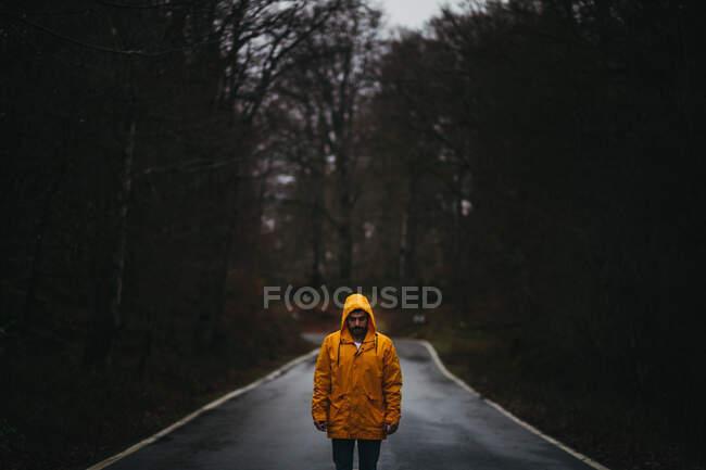 Mann in gelber Jacke blickt mit geschlossenen Augen auf leeren Asphaltweg inmitten grünen Waldes — Stockfoto