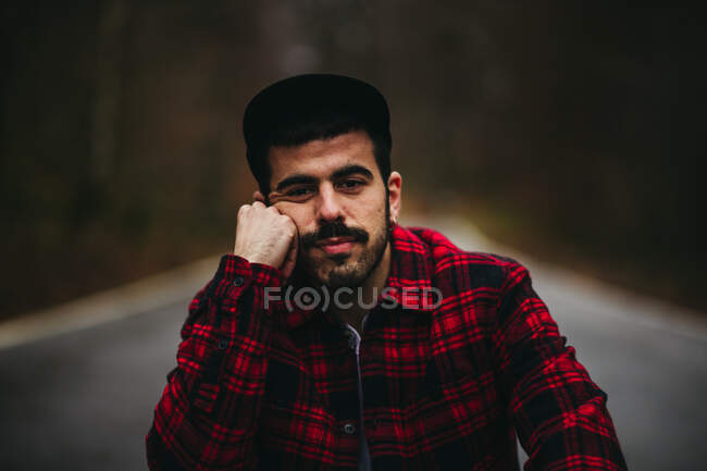 Carefree man in stylish casual wear sitting on asphalt road and looking at camera among autumn forest — Stock Photo