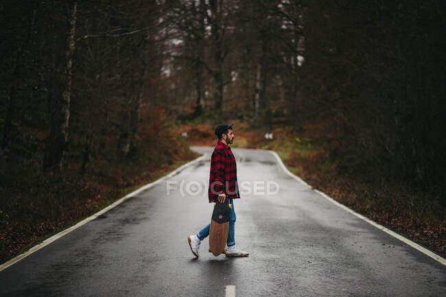 Бічний вид на молодого стильного чоловіка в повсякденному одязі ходячого по асфальтній дорозі з скейтбордом в руках восени день. — стокове фото