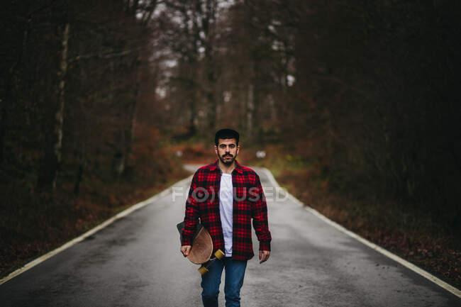 Hombre joven y elegante en ropa casual caminando por el camino de asfalto con monopatín en la mano en el día de otoño mirando a la cámara - foto de stock