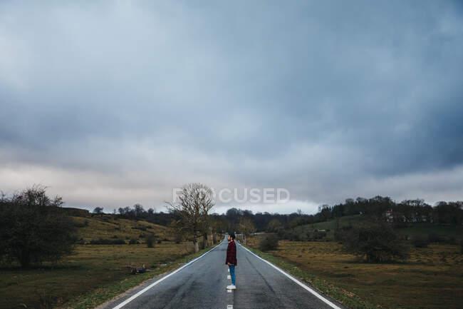 Vue latérale de l'homme en tenue décontractée marchant sur route asphaltée vide parmi les champs verts avec ciel nuageux sur fond — Photo de stock