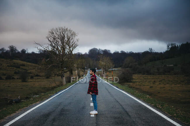 Side view of man in casual wear walking on empty asphalt road among green fields with cloudy sky on background — Stock Photo