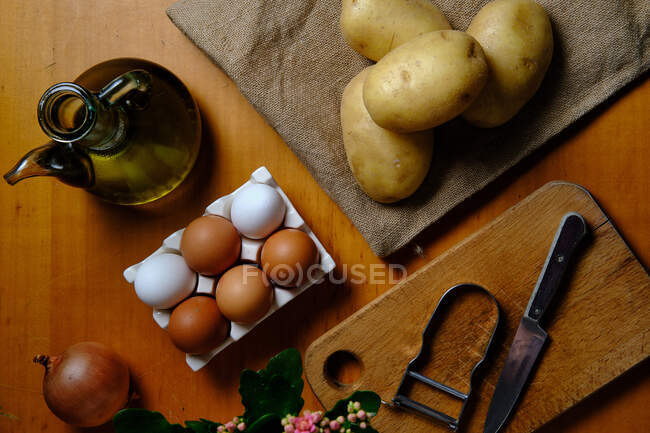 Top view of raw potatoes on table with olive oil in jar eggs onion knife and peeler on wooden cutting board in kitchen — Stock Photo