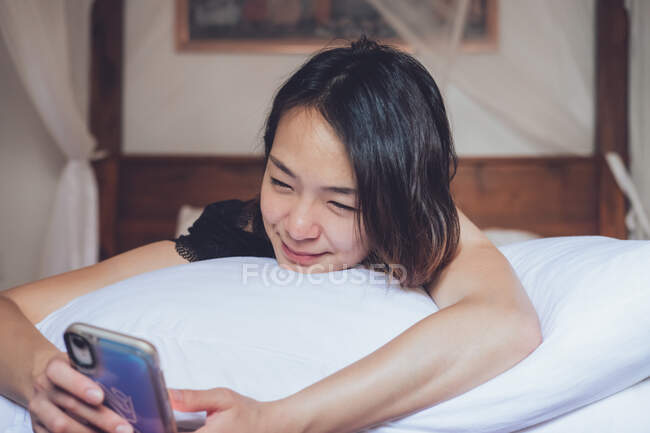Веселая этническая женщина улыбается и просматривает смартфон, лежа на подушке в удобной постели дома — стоковое фото