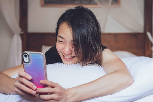 Mulher étnica alegre sorrindo e navegando smartphone enquanto deitado no travesseiro em cama confortável em casa — Fotografia de Stock