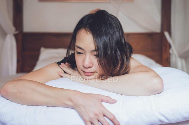 Ottimista premurosa donna asiatica distesa distesa su un comodo letto al mattino a casa — Foto stock