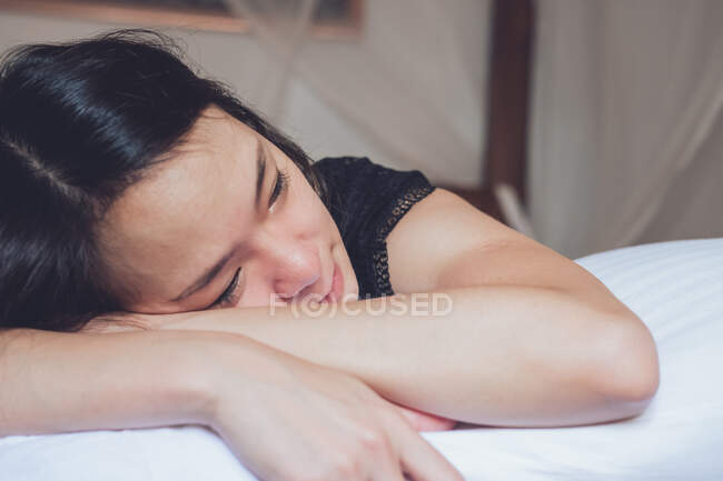 Optimistic thoughtful Asian woman looking away lying on comfortable bed in morning at home — Stock Photo