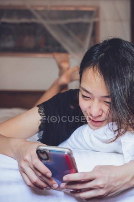 De baixo alegre feminino étnico sorrindo e navegando smartphone enquanto deitado no travesseiro em cama confortável em casa — Fotografia de Stock