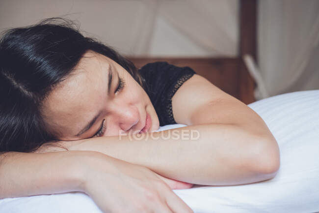 Otimista pensativo mulher asiática com os olhos fechados deitado na cama confortável de manhã em casa — Fotografia de Stock