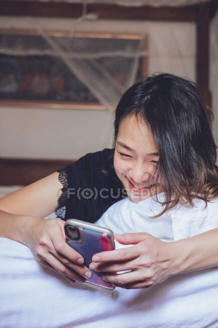 Du soufflet joyeuse ethnique souriant féminin et naviguant smartphone tout en étant couché sur l'oreiller dans un lit confortable à la maison — Photo de stock