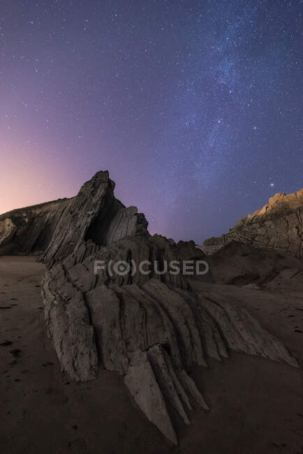 From below of rough cliff peak with colorful blue night sky and shiny stars on background — Stock Photo