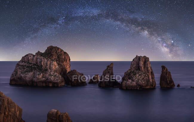 Grandes acantilados ásperos en el océano azul tranquilo durante la noche brillante bajo el cielo estrellado colorido con la vía láctea - foto de stock