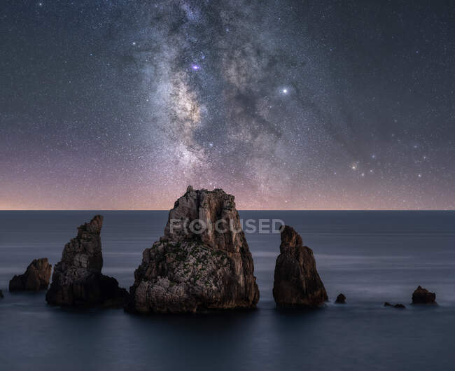 Big rough cliffs on blue calm ocean during bright evening under colorful starry sky with milky way — Stock Photo
