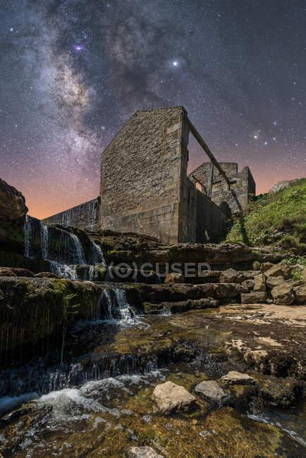 Desde abajo del antiguo castillo de piedra y pequeña cascada en las escaleras bajo el cielo oscuro con estrellas y la vía láctea - foto de stock
