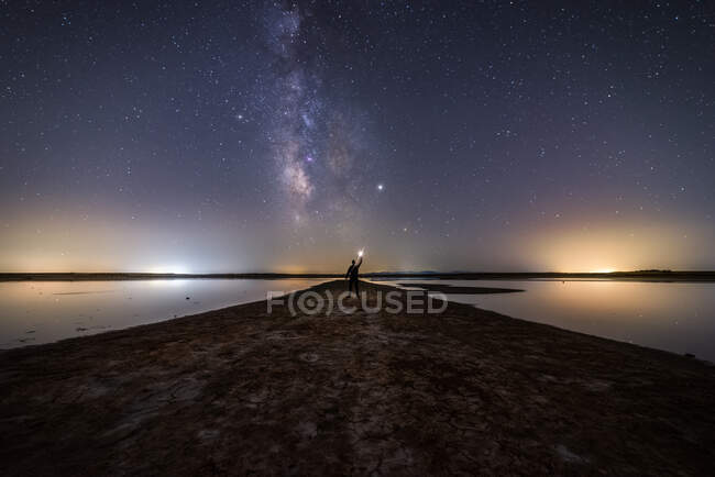 Back view of anonymous man standing on empty road among calm water and reaching out to star under colorful nigh sky with milky way on background — Stock Photo