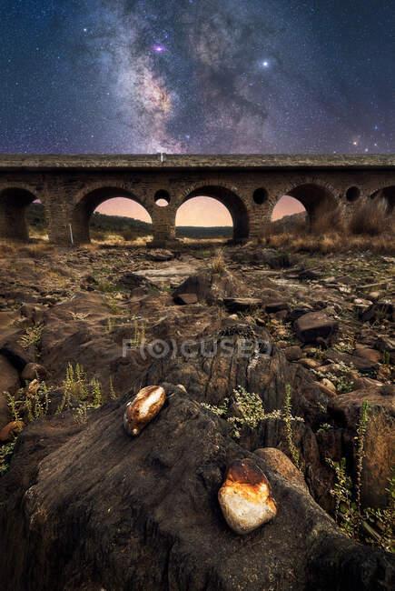 Sol rocheux et vieux pont en pierre avec ciel nocturne coloré avec voie lactée et étoiles sur le fond — Photo de stock