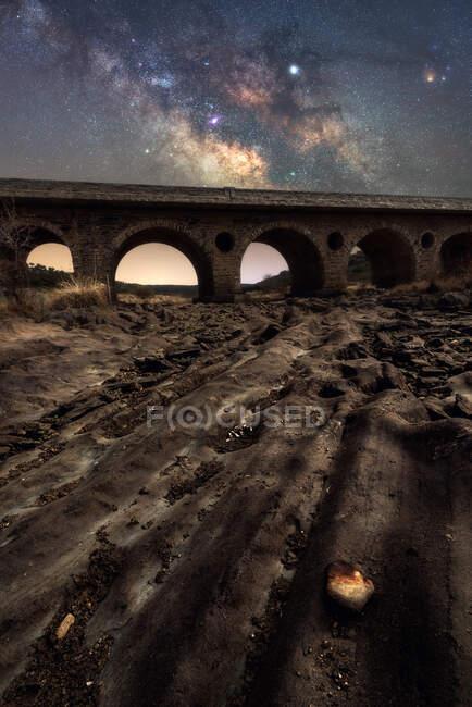 Скелястий ґрунт і старий кам'яний міст з барвистим нічним небом з молочним шляхом і зірками на задньому плані — стокове фото