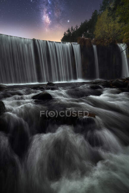 Beautiful powerful rocky waterfall and stream of water with colorful night starry sky on background — Stock Photo